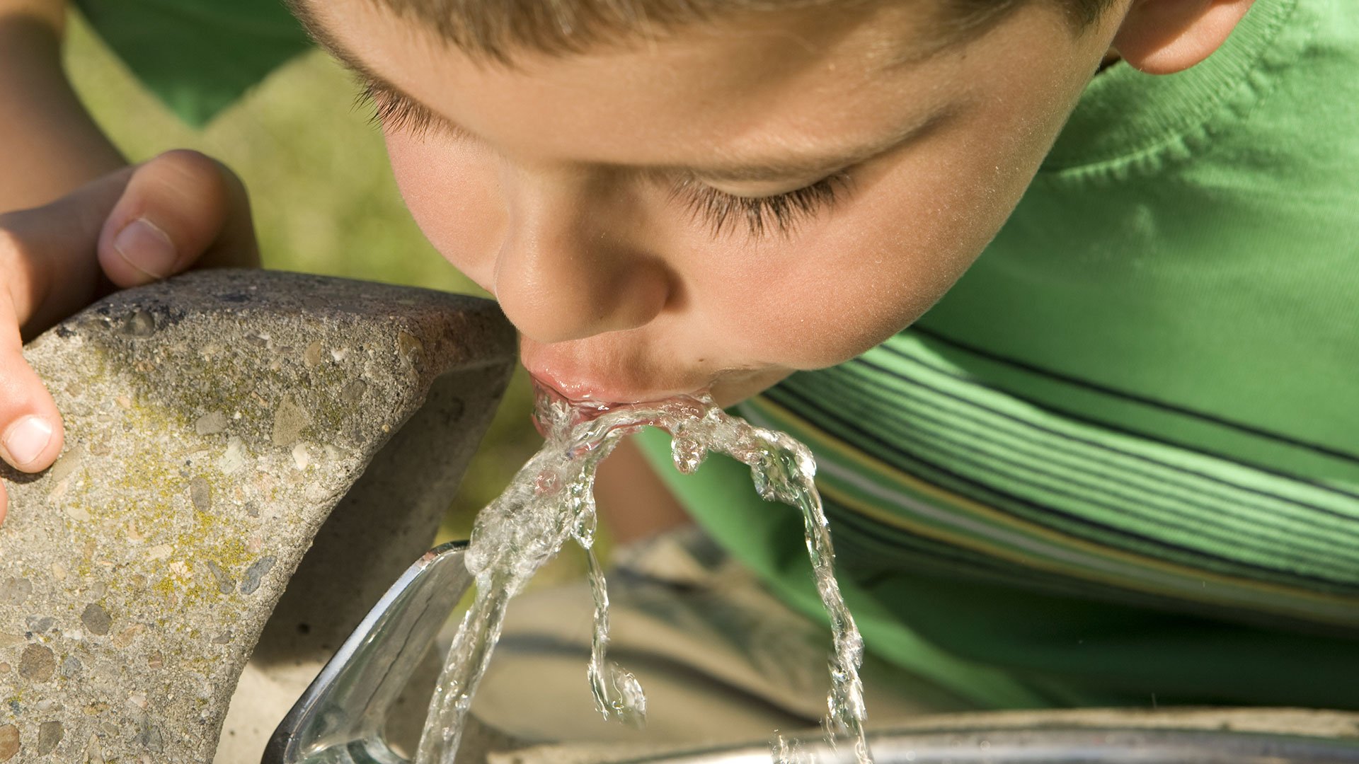 young boy drinking water from fountain